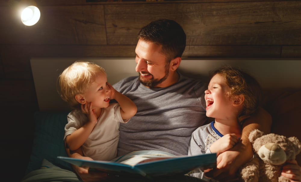 The Car Bed Shop explain the value of a healthy bedtime routine for your child - Dad doing bedtime stories